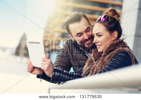 Picture of young couple using tablet outdoors
