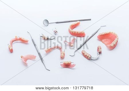 Set of dentures and dental tools on white background
