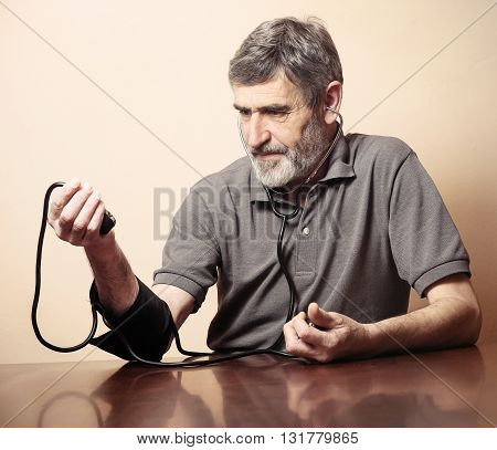 Senior man measuring blood pressure at home