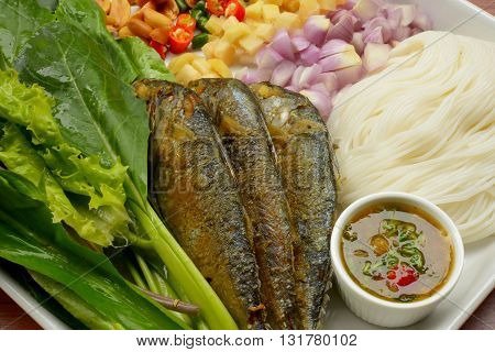 Thai style fried mackerel fish serving with fresh salad , rice noodle and spicy dressing sauce