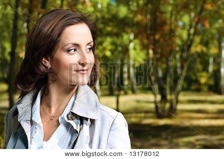 Beautiful woman walking at the autumn park.