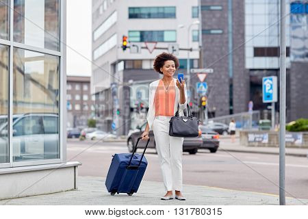 travel, business trip, people and technology concept - happy young african american woman with travel bag and smartphone on city street