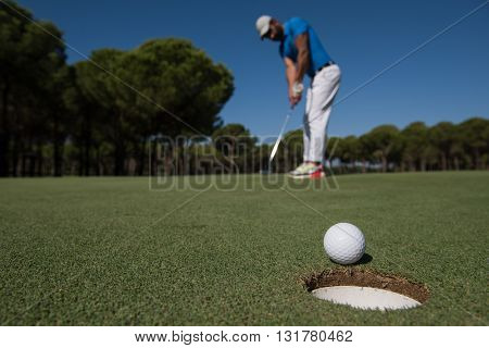 golf player hitting shot with driver, ball on edge of  hole  on course in background  at beautiful sunny day