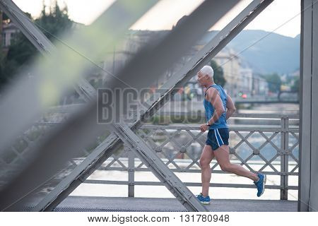 handsome senior man athlete jogging and  have morning workout with sunrise and city in background