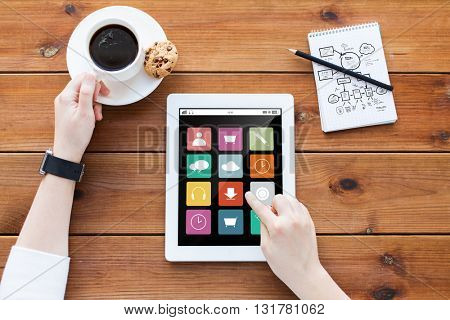 business,  technology, media and people concept - close up of woman with menu icons on tablet pc computer screen, notebook and coffee on wooden table