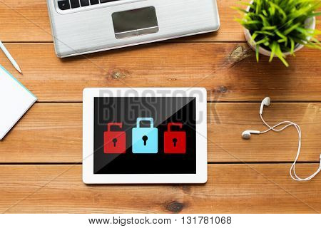 business, cyber protection, web security and technology concept - close up of tablet pc computer, laptop and earphones on wooden table with padlock icons on screen