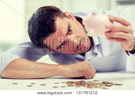 business, people, finances, crisis and money saving concept - businessman shaking piggy bank and getting coins at office