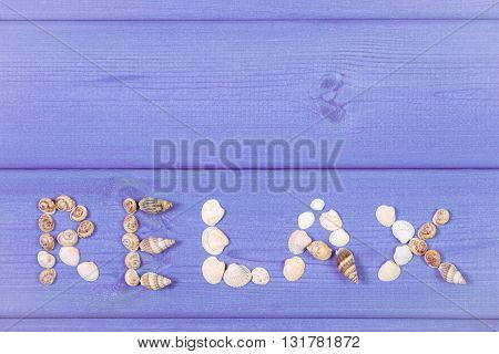 Inscription relax made of seashells on purple boards summer and vacation time copy space for text