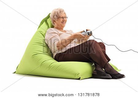 Elderly lady playing video games seated on a comfortable green beanbag isolated on white background