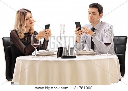 Young man and woman sitting on a date and looking at their cell phones isolated on white background