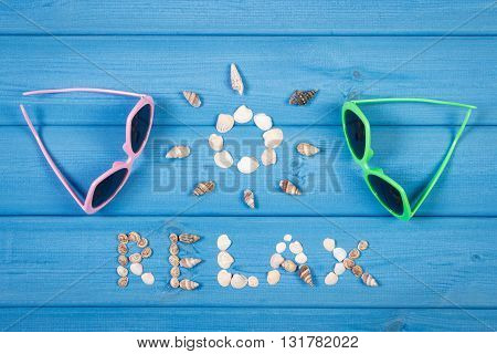 Inscription relax and shape of sun made of seashells sunglasses on blue boards summer and vacation time