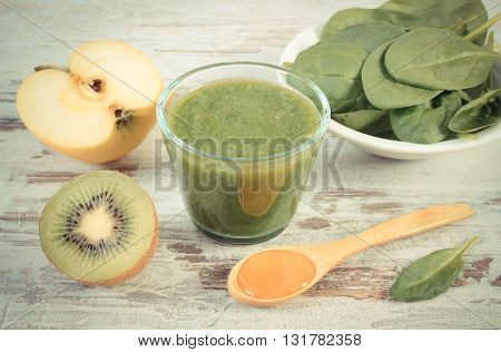Vintage photo nutritious cocktail from spinach apple and kiwi with honey on old rustic wooden background healthy nutrition