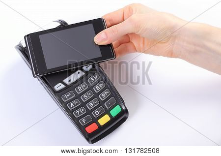 Banking and finance concept Hand of woman using payment terminal with mobile phone with NFC technology credit card reader