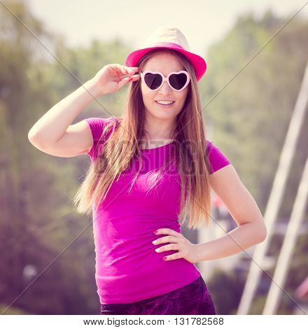 Happy smiling woman tourist with straw hat and sunglasses in shape of heart in port with yacht in background travel summer and vacation time