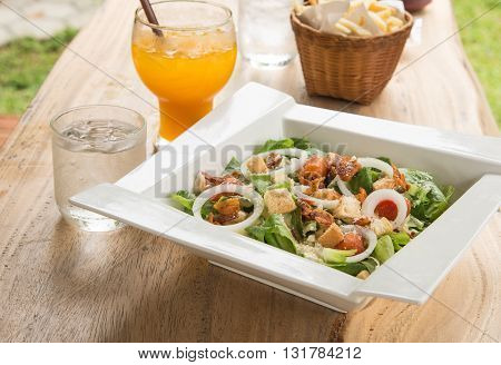 Caesar salad in White plate Orange juiceGlass of water placed on wooden table.
