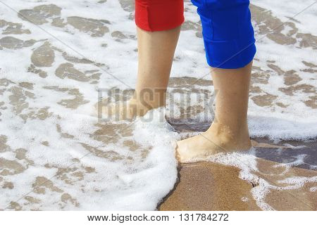 Beautiful woman legs with tucked up trousers walking on a beach.