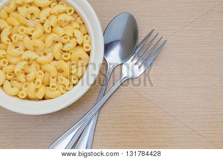 Macaroni in white bowl with spoon and folk on wooden table