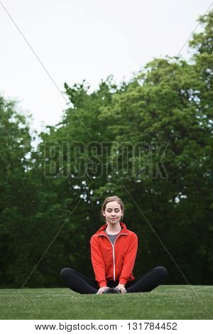 Young female athlete in red and black sportswear meditating while sitting on green grass in park. Smiling lady looking at camera anf trying to concentrate.