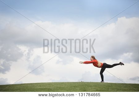 Picture of sport woman training in green park or forest. Young beautiful lady in red jacket training with nature during sunset or sunrise.