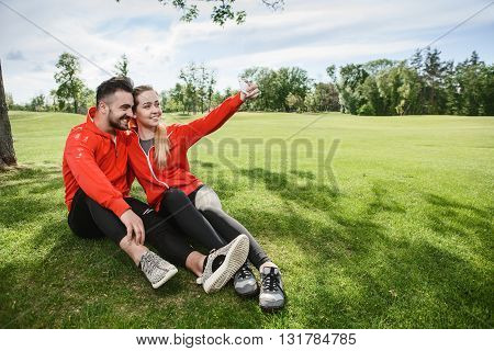 Sport man and woman making selfies in green park or forest while sitting on green grass. Happy couple hugging and posing for camera.
