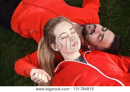 Portrait of sport man and woman in red jackets resting in green park. Tired and exhausted couple sleeping on green grass after training.