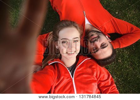 Happy sport man and woman making selfies in green park while lying on green grass after hard-working training: jogging, jumping, etc.