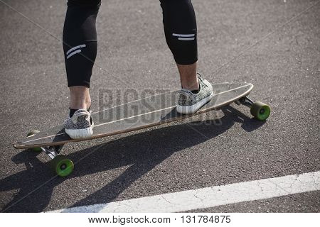 Man riding on longboard skate on road through forest or city. Man's legs on skateboard or longboard.