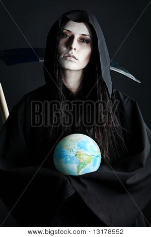 Woman death reaper with a globe over black background. Halloween.