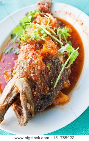Fried grouper fish with saucesour and spicy on white plateThai style food.