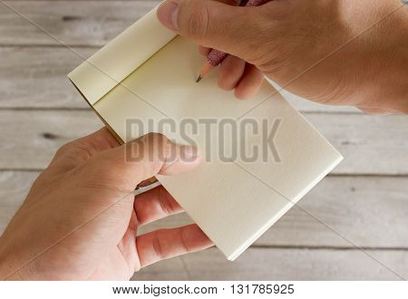 Pencils and notebook in hand with wood background