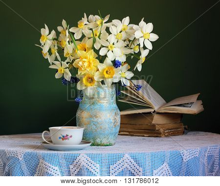 Retro still life with daffodils Cup and books in the background on round table with blue tablecloth with lace.