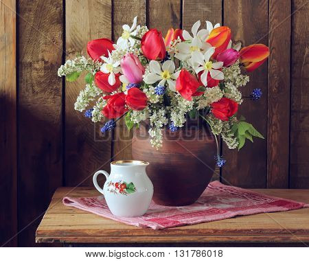 Still life spring bouquet of daffodils and tulips in a clay jug on a wooden table in rustic style.