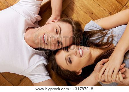 Happy couple lying on the floor.