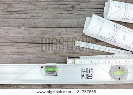 Blueprints With Folding Rule And Spirit Level On Gray Wooden Desk