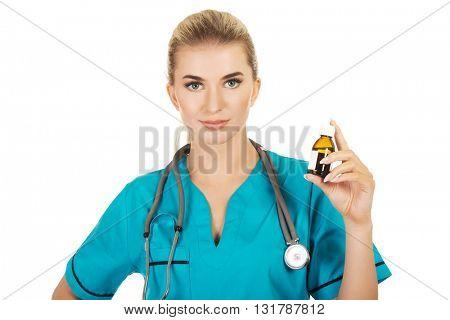 Female nurse or doctor holding medicine bottle in the hand