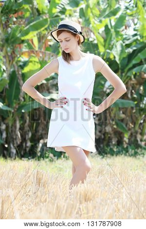 Outdoor portrait of girl posing in the dry rice field in the white dress and straw hat