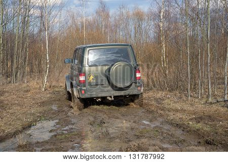 LENINGRAD REGION, RUSSIA - APRIL 16, 2016: The car UAZ-Patriot is stuck in the mud while crossing the forest belt