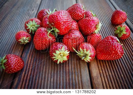 Fresh garden strawberries on old wooden background