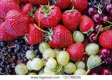 Mix of fresh and juicy berries in the summer garden on wooden texture background