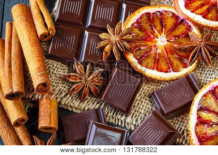 Dark chocolates with dry oranges cinnamon and anise on burlap on rustic table