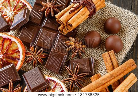 Dark and milk chocolates with dry oranges candies cinnamon and anise on burlap on rustic wooden table