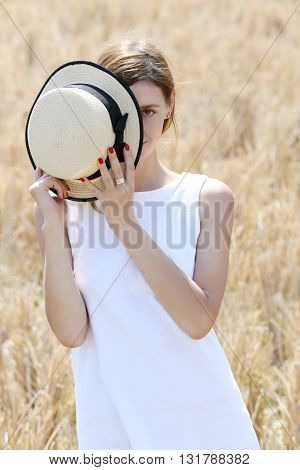Outdoor portrait of girl in the white dress holding straw hat