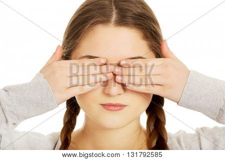 Teen woman covering her eyes.