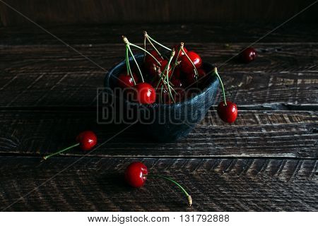 red cherries in a black ceramic cup red cherries red cherries on a brown background bowl with cherries.