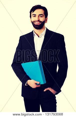 Handsome businessman holding a binder.
