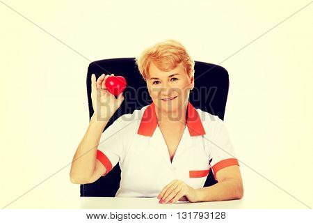Smile elderly female doctor or nurse sitting behind the desk and holds heart toy
