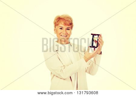 Smile elderly  business woman holding sandglass