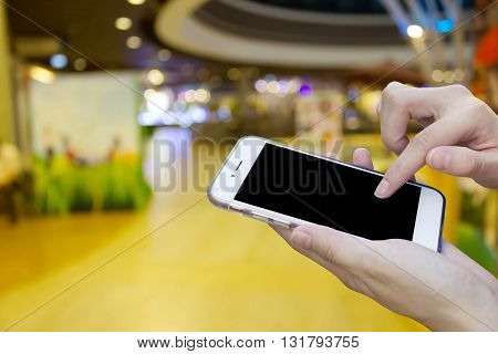 Woman using touch screen mobile phone with blur shopping mall