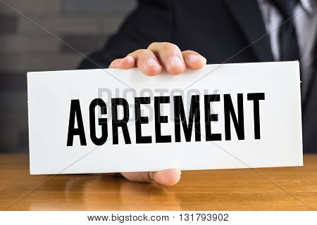 Agreement message on white card and hold by businessman