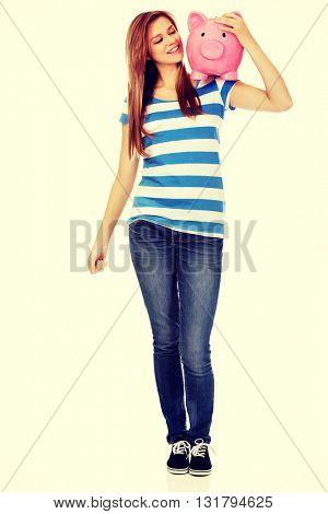 Happy teenage woman holding piggybank